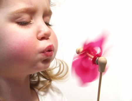 little girl blowing a pink pinwheel