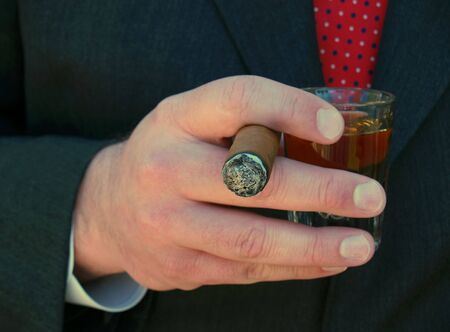 man in suit smoking a cigar and holding a shot of whiskey Stock Photo