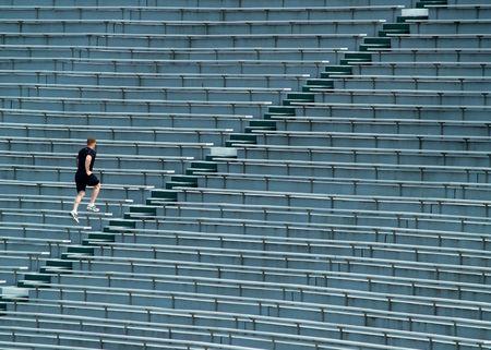 climbing stairs: L'uomo in esecuzione fino allo stadio bleachers  Archivio Fotografico