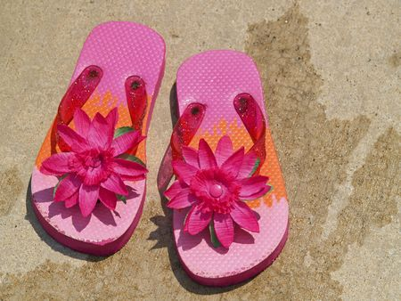 pink flip flop sandals on wet cement surrounding a swimming pool