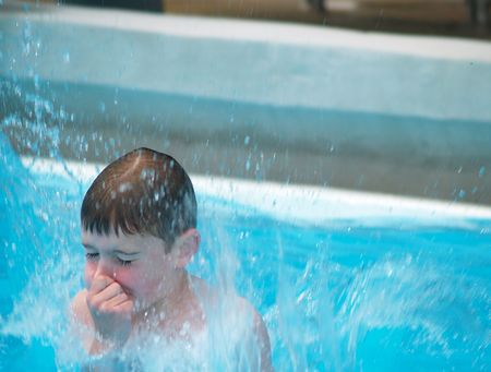 boy jumping into a swimming pool while holding his nose Stock Photo