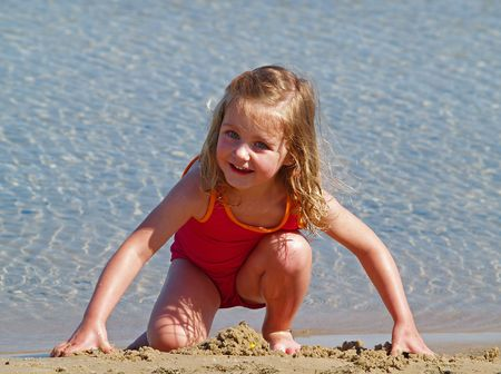children sandcastle: young girl playing in sand at the beach