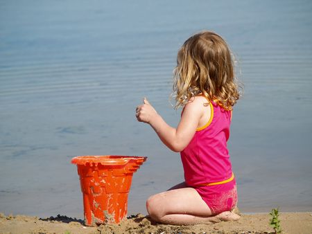 children sandcastle: young girl playing with a bucket in the sand at the beach