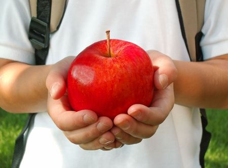 boy holding a red apple for his teacher on the first day of school