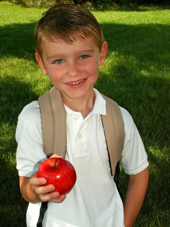 first day: boy taking an apple for his teacher on the first day of school