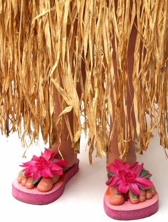 bottom half of a girl wearing a grass hula skirt and pink flowered flip flop sandals