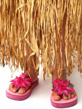 flops: bottom half of a girl wearing a grass hula skirt and pink flowered flip flop sandals