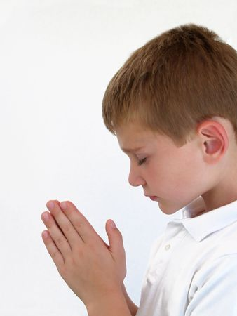 Young boy praying with hands together Stock Photo
