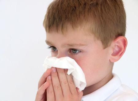 病気の少年が彼の鼻を吹いています。
