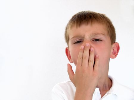 boy covering his mouth while yawning Stock Photo