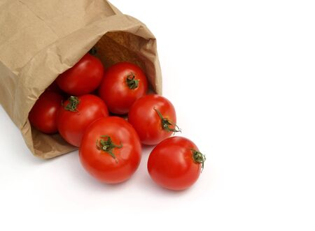 tumbling: red ripe tomatoes tumbling out of a brown paper bag