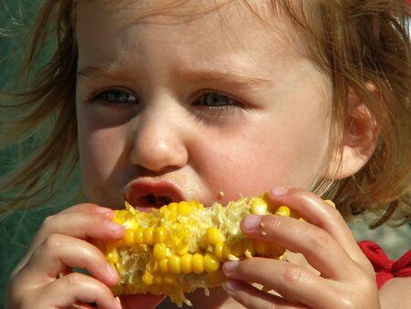 小さな女の子の団子乱雑なトウモロコシを食べる