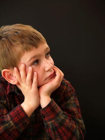若い男の子の彼の手に彼の顔を休んで格子縞のフランネル シャツ