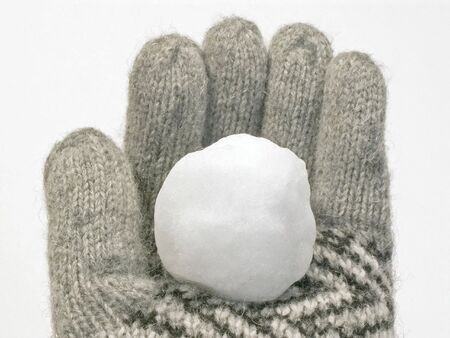 snowball in a gray knit glove Reklamní fotografie