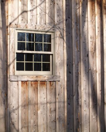 window in a wood cabin with tree shadows