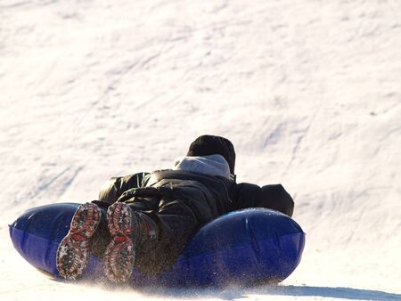 boy sledding down a snowy hill on a blue inflatable sled photo