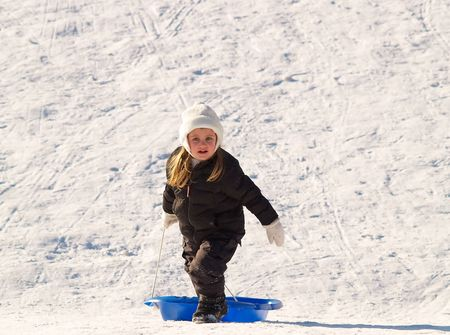 little girl pulling her blue sled up the snowy hill photo