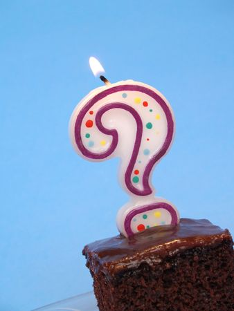 birthday cake with a question mark candle lit on top photo