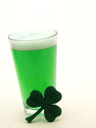 Green beer in a pint glass with a decorative shamrock for St Patricks Day