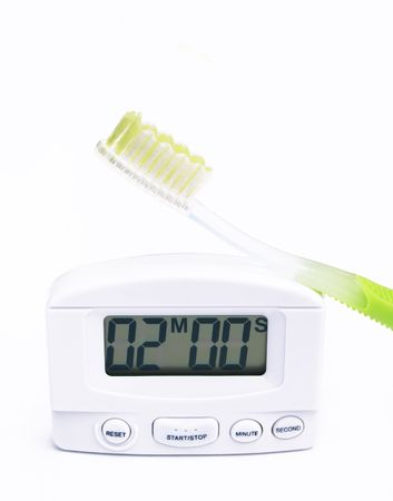 timer set for two minutes and a green handled toothbrush