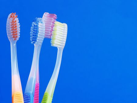orange, blue, pink and green toothbrushes over blue Stock Photo - 834927