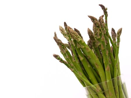 green asparagus spears staying fresh in a glass of water Banco de Imagens