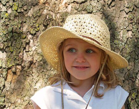 little girl in big straw sun hat leaning against tree bark Stock Photo