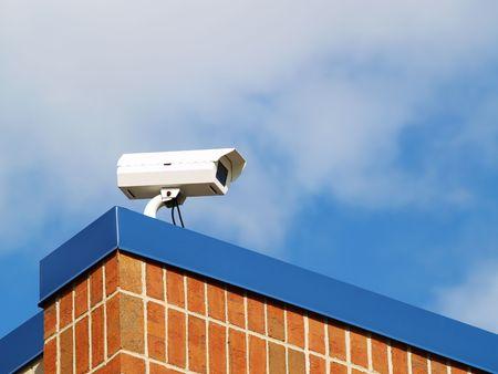 a security camera mounted atop a brick building