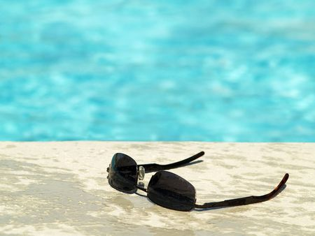 black sunglasses on the deck beside a swimming pool photo