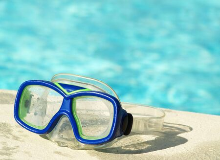 blue swim mask beside the pool