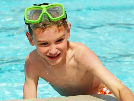 swimming trunks: young boy climbing out of a swimming pool Stock Photo