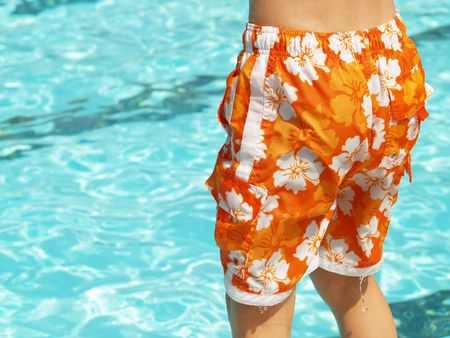 wet suit: boys orange flowered swimsuit dripping beside the pool Stock Photo