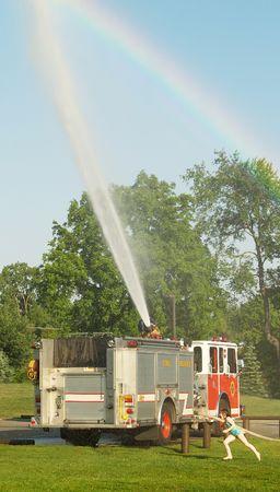little girl running through the spray of a fire truck Stock Photo - 1201308