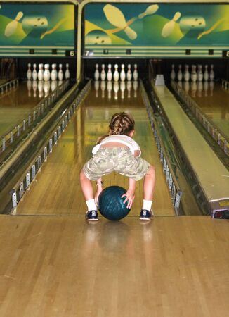 a little girl playing a game of bumper bowling Stock Photo