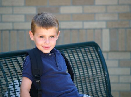 young boy waiting at the school bus stop photo