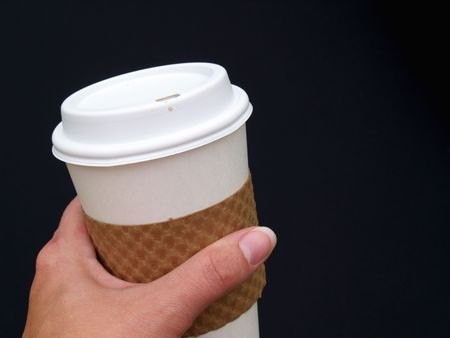 a females hand holding a disposable paper coffee cup Stock Photo