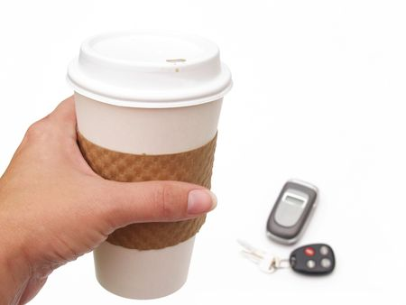 hurried: femalae hand holding disposable coffee cup with keys and cell phone in background Stock Photo