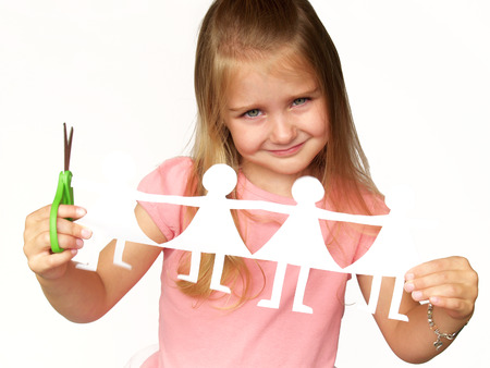little girl holding up paper dolls and scissors Stock Photo