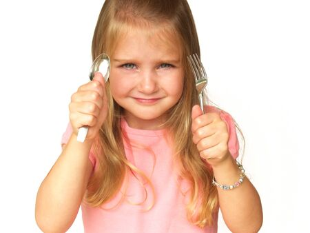 little girl holding up a fork and spoon Stock Photo