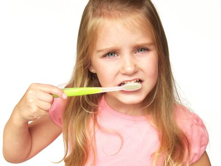 little girl brushing her teeth with a green toothbrush Stock Photo