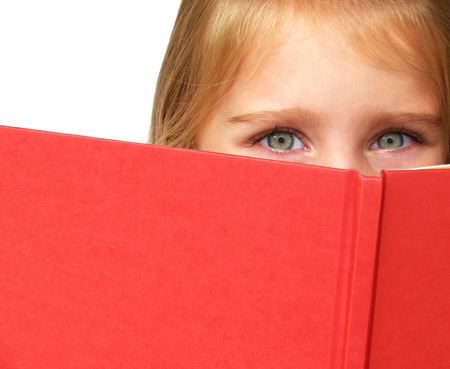 a little childs eyes looking over the top of a book Stock Photo