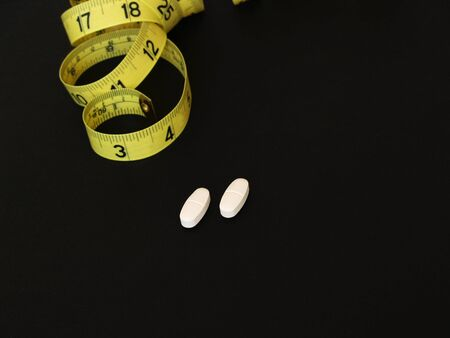 fad: diet - two supplements with a yellow tape measure in the background