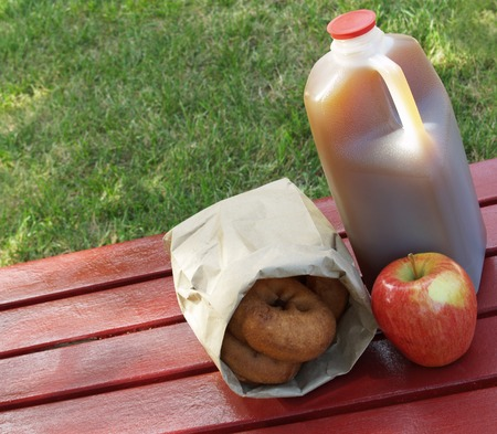 fall - an apple, a jug of apple cider and a bag of donuts on a red picnic table Stock Photo