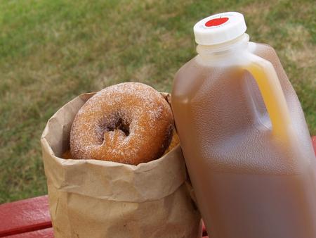 a half-gallon of apple cider alongside a bag of cinnamon-sugared donuts