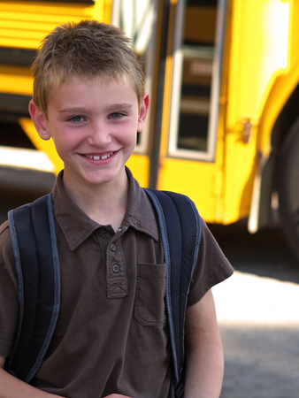 a smiling school boy with a yellow school bus in the background