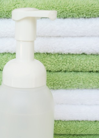 foaming handsoap in front of a stack of bath towels - focus on bubbles Stock Photo