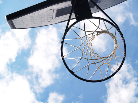 basketball hoop against blue sky with fluffy clouds Stock Photo