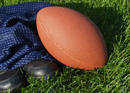 An American football, jersey and cleats on turf Stock Photo