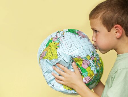 cure: young boy breathing life back into a deflating planet earth Stock Photo