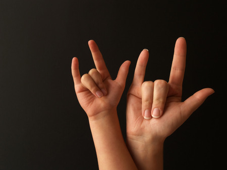 a mother and her child doing sign language for I LOVE YOU